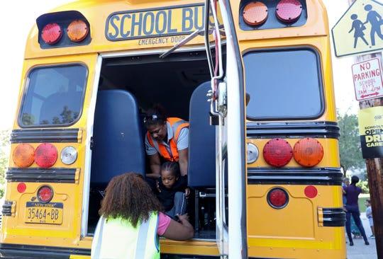 Bus driver Celeste Nunez hands pre-kindergartener Judah Saintil, 3, to bus monitor Margarita Nunez during an emergency drill at Pearls Hawthorne School in Yonkers in August 2019.