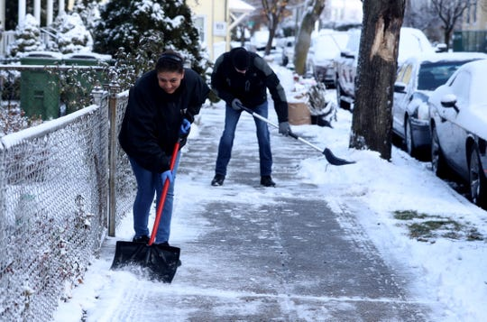 Blanca Alvarez and Ron Cafarelli of Tarrytown shovel snow from the sidewalk in front of their homes Dec. 3, 2019.