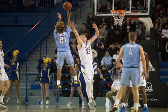Delaware's Collin Goss (33) attempts to block a shot from Columbia's Mike Smith (21) Monday night at the Bob Carpenter Center. Delaware beat Columbia 84-76 to stay undefeated at 9-0.