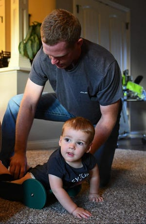 Taylor Moreland adjusts the straps of The Frog for his son Brody, 2, on Oct. 15 at their home in Centralia. Taylor designed The Frog so Brody, who has spina bifida and is paralyzed from the rib cage down, could move around independently.