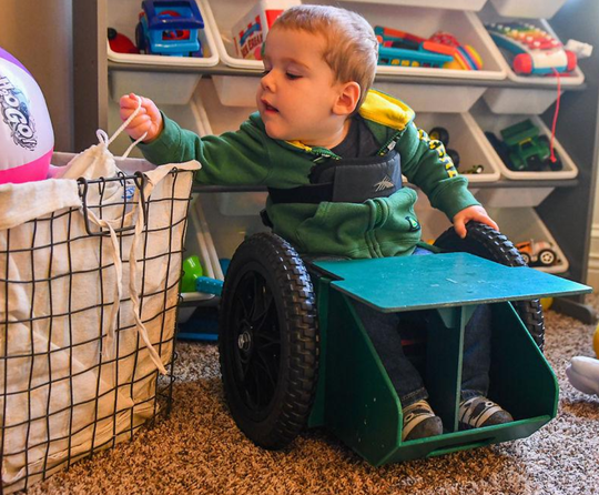 Brody Moreland, 2, reaches for his toys while in his GoBro, a wheelchair his parents designed for him, Oct. 15 at his home in Centralia. Brody uses a larger wheelchair when he is outside his home, but the GoBro is perfect for reaching and playing with his toys around the house.