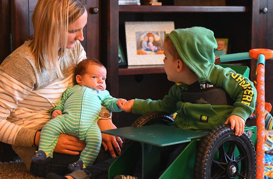 Brody Moreland, 2, reaches out for the hand of his month-old baby brother, Brett, as their mom, Ally Moreland, watches at their home in Centralia. She says he loves spending time with his new brother