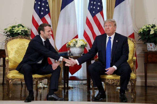 US President Donald Trump and France's President Emmanuel Macron shake hands during their meeting at Winfield House, London on December 3, 2019. NATO leaders gathered on Dec. 3 for a summit to mark the alliance's 70th anniversary but with leaders feuding and name-calling over money and strategy, the mood is far from festive.