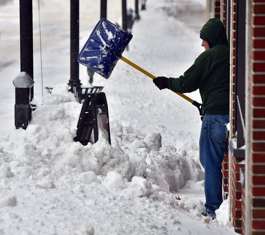 Rick Silver clears snow from the front of his brother-in-law's store, Gardner Coins & Cards, Monday, Dec. 2, 2019, in Gardner, Mass.