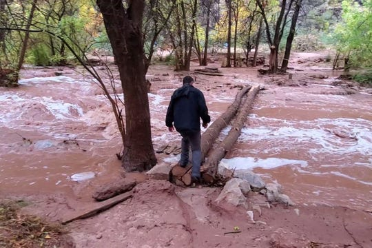 In this Nov. 29, 2019, photo, an unidentified man is seen crossing a flooded campground in Supai, Arizona. The flood happened just days before the Havasupai Tribe shuts down its reservation to tourists for the season. No one was injured, but some tourists woke up drenched and some lost camping gear.