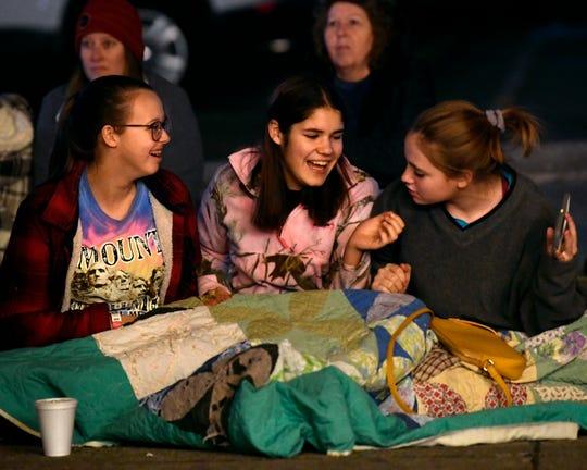 Audry Meffert, 14, (left), McKenzie Reyna and Addison Koslan, both 13, laugh while watching last week's City Sidewalks Christmas Lights Parade along Cypress Street.
