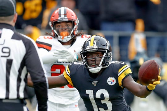 Pittsburgh Steelers wide receiver James Washington (13) looks to the official for the call after making a catch in the end zone as Cleveland Browns defensive back Sheldrick Redwine (29) waves his hands during the first half Sunday, Dec. 1, 2019, in Pittsburgh. The catch was ruled a touchdown.