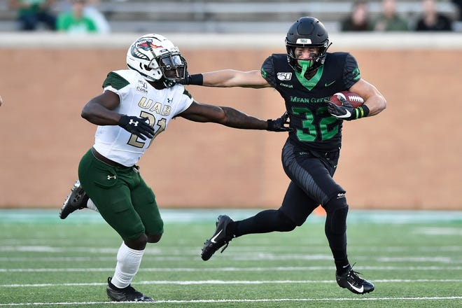 North Texas wide receiver Michael Lawrence (32) stiff-arms UAB defensive back Will Dawkins (21) during the second half Saturday, Nov. 30, 2019, in Denton, Texas.