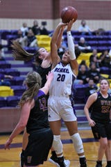Merkel's Alyssa White (20) tries to get a shot off while Wylie's Karis Christian (12) goes for a block on Tuesday. White scored four points and grabbed seven rebounds in the 31-18 victory.