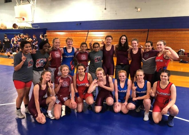 Female wrestlers from West Henderson and Swain County pose for a picture after Tuesday night's historic match.