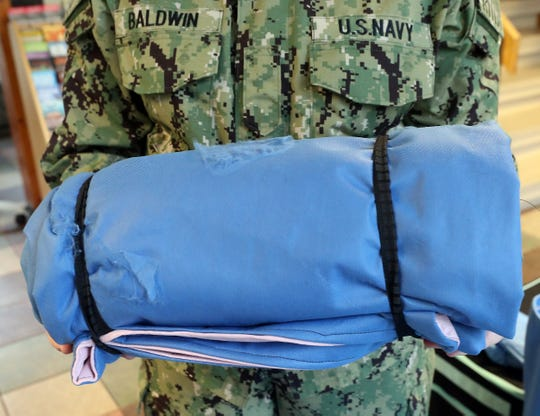 Naval Hospital Bremerton Hospitalman Cozzette Baldwin holds a sleeping pad in a bag, all crafted of blue muslin used in operating rooms. Baldwin came up with a way to sew the muslin, which is waterproof, into the pads and bags.