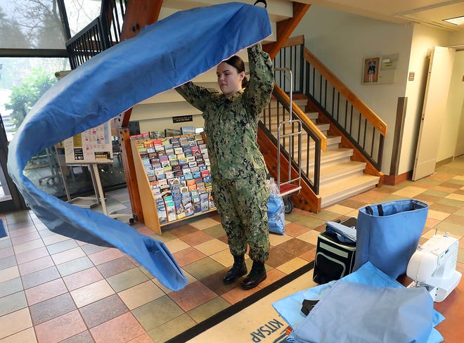 Naval Hospital Bremerton Hospitalman Cozzette Baldwin unrolls one of the sleeping pads that was made from blue muslin wrap. The wrap is used to briefly cover medical instruments in the operating room but quickly pulled off and disposed of. Baldwin has found a way to repurpose them into sleeping pads to distribute to the homeless.