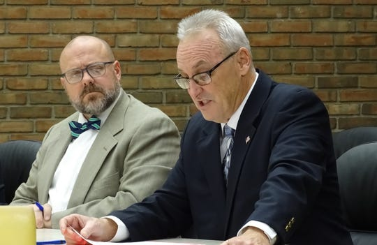 Kevin Myers, left, listens as Dan Wirebaugh speaks against a proposal to extend the residency requirement for the city's service-safety director to a 20-mile radius during Tuesday's Bucyrus City Council meeting.