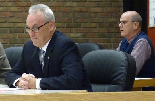 Council member Dan Wirebaugh, left, listens as Mayor Jeff Reser speaks in defense of a proposal to extend the residency requirement for the city's service-safety director to a 20-mile radius during Tuesday's Bucyrus City Council meeting.