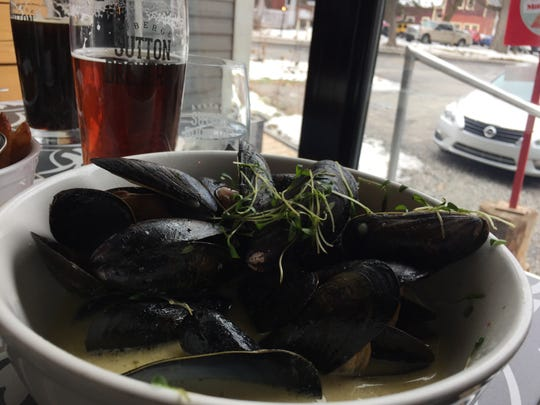 A bowl of mussels and fries with fresh beer at Microbrasserie Auberge Sutton Brouerie in Quebec.