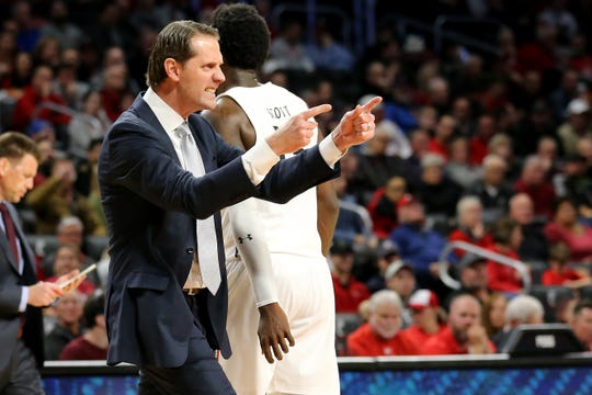 Cincinnati Bearcats head coach John Brannen instructs the team during a timeout in the second half of a NCAA college basketball game against the Vermont Catamounts, Tuesday, Dec. 3, 2019, at Fifth Third Arena in Cincinnati.