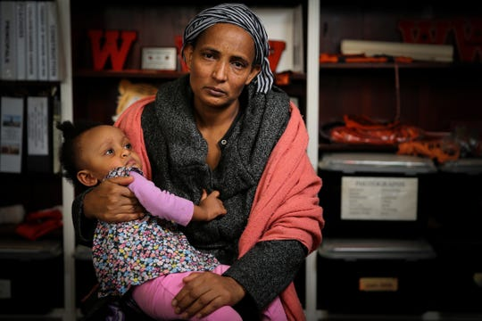 Taemut Gebrehmedhin, 40, whose daughter, Ziada Berhane, 17, died suddenly in October, sits for a portrait with her one and half-year-old daughter, Mieraf, Tuesday, Dec. 3, 2019, at Withrow High School in Cincinnati. Ziada died as a result of disseminated intravascular coagulation due to a cardiac arrhythmia, according to the Hamilton County Coroner's office.