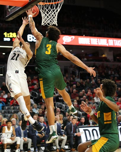 Cincinnati Bearcats guard Jaevin Cumberland (21) goes up for a layup as Vermont Catamounts forward Anthony Lamb (3) defends during the second half of a NCAA college basketball game, Tuesday, Dec. 3, 2019, at Fifth Third Arena in Cincinnati.