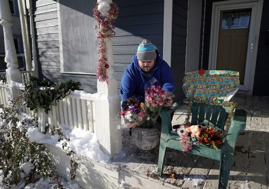 Neighbor Eric Stiver put flowers and stuffed animals on a chair on Monday, Dec. 2, 2019, on the porch of the home where a deadly shooting occurred in Minneapolis.