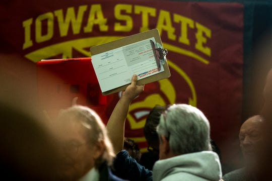A campaign worker holds up a clipboard with commit to caucus cards during an event with Former Vice President Joe Biden in the South Ballroom inside the Iowa State University Memorial Union on Wednesday, Dec. 4, 2019, in Ames.