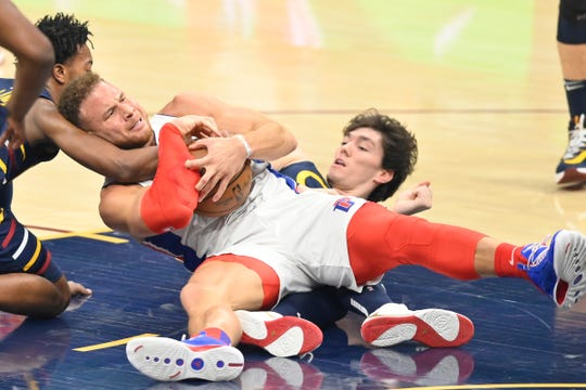 Detroit Pistons forward Blake Griffin (23) fights to keep control the ball defended by Cleveland Cavaliers guard Darius Garland (10) and forward Cedi Osman (16) in the first quarter at Rocket Mortgage FieldHouse on Tuesday, Dec. 3, 2019.