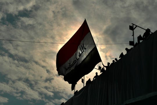Anti-government protesters wave a flag while standing on a building near Tahrir Square during ongoing protests in Baghdad, Iraq, Sunday, Dec. 1, 2019.