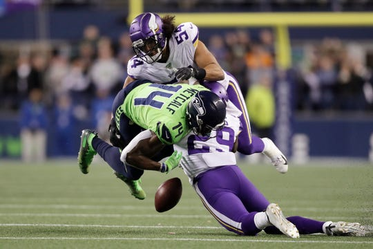 Minnesota Vikings' Xavier Rhodes (29) and Eric Kendricks (54) hit Seattle Seahawks' DK Metcalf (14), who fumbles Monday.