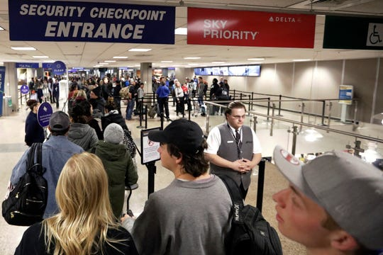 Travelers walk through a security checkpoint in Terminal 2 at Salt Lake City International Airport, in Salt Lake City.