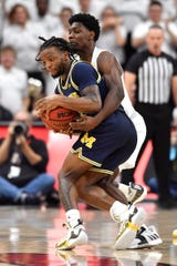 Louisville guard Darius Perry (2) attempts to strip the ball away from Michigan guard Zavier Simpson (3) during the second half Tuesday. Louisville won 58-43.