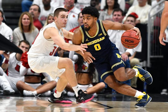 Michigan guard David DeJulius (0) attempts to drive past the defense of Louisville guard Ryan McMahon (30) during the second half.