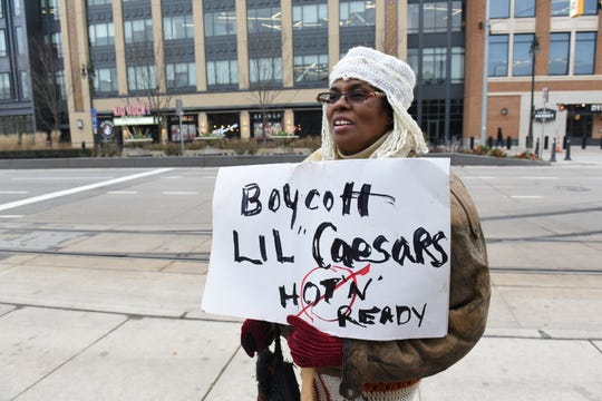 Tahira Ra of Detroit protests outside Kid Rock's Made In Detroit restaurant at Little Caesars Arena Wednesday after the musician announced that he will not renew the restaurant's license.