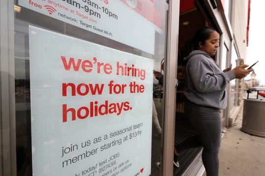A passer-by walks past a hiring for the holidays sign near an entrance to a Target store location, in Westwood, Mass.