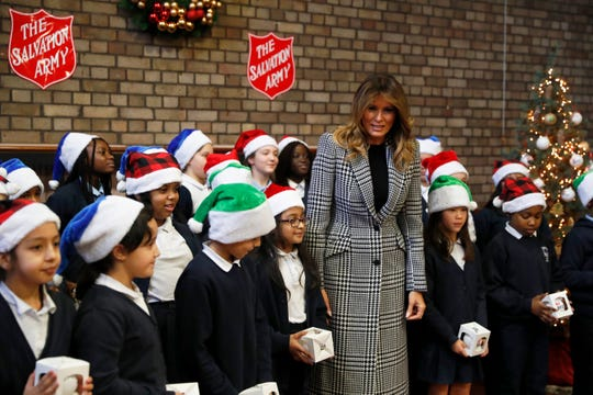 First lady Melania Trump poses with a children choir after joining local students and U.S. Marines stationed at the U.S. Embassy, wrapping holiday presents to be donated to the Salvation Army, at the Salvation Army Clapton Center in London, Wednesday, Dec. 4, 2019.