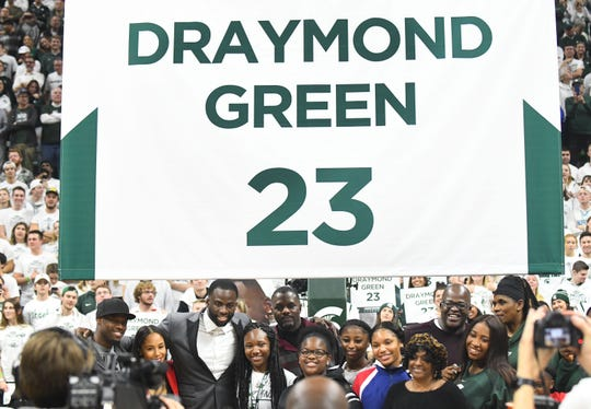 Former Michigan State basketball player Draymond Green and his family pose under his number during a halftime presentation retiring his number.