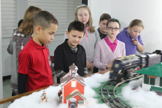 Lutz Elementary fourth graders Evan Butler, 9, left, Jhadyn Abdoo, 10, middle, and Mady Meyer, 9, right, watch as model trains drive by at the Hayes exhibit room.