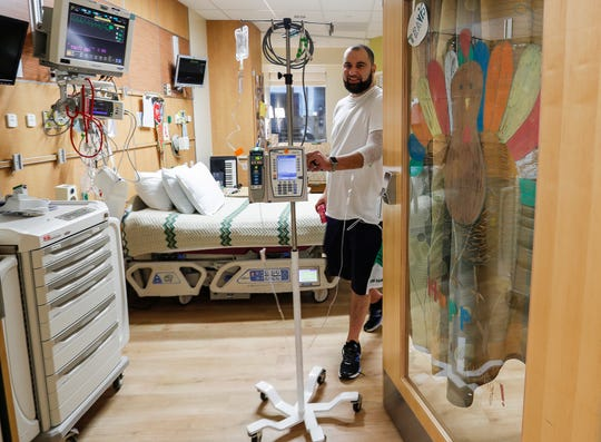Travis Ballard, 38, born with a congenital heart defect, walks out of his room at Riley Hospital for Children, Indianapolis, Nov. 27, 2019. Every 30 days, Ballard and other patients change rooms, but keep the cards and pictures to decorate doorways and walls.