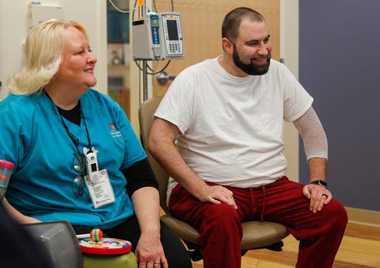 Travis Ballard, 38, smiles at another patient during a music therapy session at Riley Hospital for Children, Indianapolis, Wednesday, Dec. 4, 2019. Ballard was born with a congenital heart defect and has been at Riley's Children Hospital for 164 days waiting for a heart transplant.