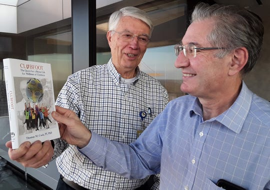 Author Tom Cook (left), professor emeritus at the University of Iowa, shows a copy of his just-released book on Dr. Ignacio Ponseti to friend and colleague Dr. Jose Morcuende, who trains doctors worldwide in the Ponseti Method for correcting clubfoot.