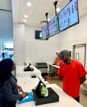 Mercedes Bush of Holmes County places an order with B.J. Williams, an employee at The Baked Stuffed Potato Factory, which is located at Northpark.