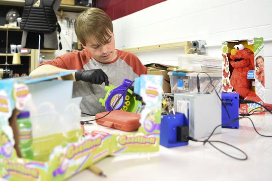 Cody James, a member of Knox Makers, rewires an electronic bubble making machine so that it can be operated by a large push button at Spark's Toy Adaption Night on Tuesday, December 3, 2019 at the Knox Makers facilities below the Spark headquarters.
