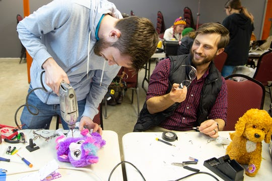 Brandon Schreiber drills a hole into a toy's battery compartment while adapting to be operated by children with disabilities at the Knox Makers workshop on Tuesday, December 3, 2019. Schreiber is a member of Knox Makers, along with other volunteers like Garrett Bentley, are volunteering their evening to adapt toys for Spark.