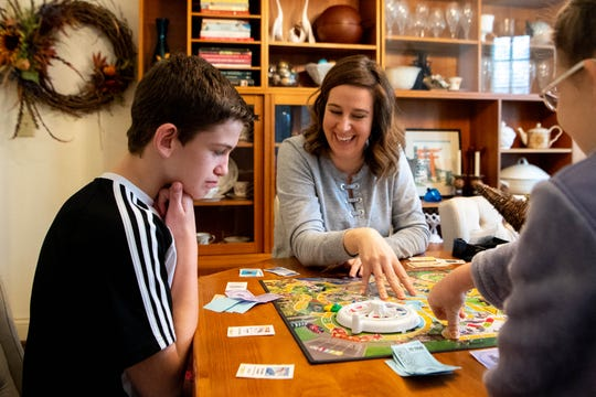 Ethan, 13, Beth, and Kate Woodruff, 10, (from left) play the Game of Life at their home Tuesday, Nov. 26, 2019 in Nashville, Tenn.