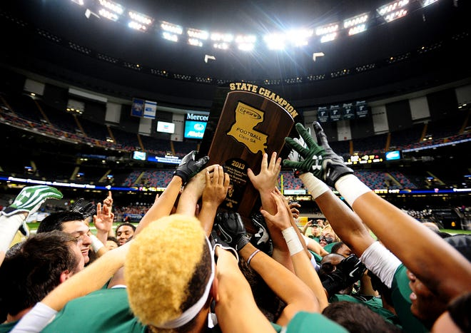 Acadiana players hoist the championship trophy over their heads after their victory over Parkway in the the LHSAA Class 5A State Championship game at the Mercedes-Benz Superdome in New Orleans, LA, Saturday, Dec. 14, 2013. Acadiana defeated Parkway 77-41.