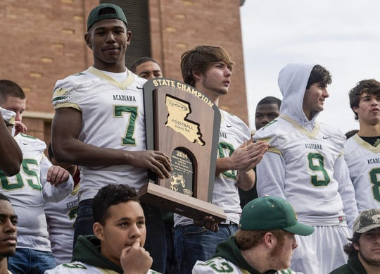 Acadiana High School quarterback Kevin Moore (7) holds the LHSAA Class 5A State Championship trophy during a victory celebration at Scott City Hall on Jan. 4, 2015. The town held a celebration following the team's second consecutive championship after their 23-7 victory over Destrehan in December.