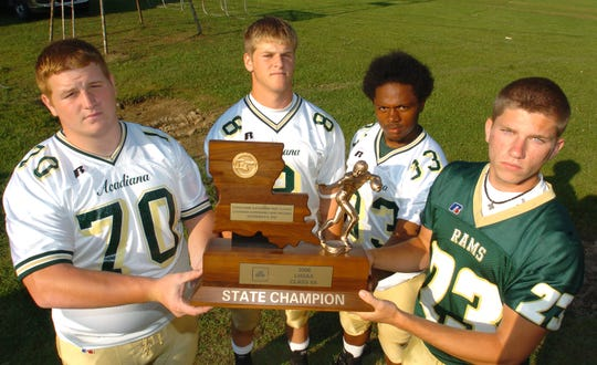 Offensive lineman Ethan Piazza, quarterback Johnathan Morvant, running back John Dean and kicker Drew Alleman with the State Football trophy May 11, 2007, in Scott.