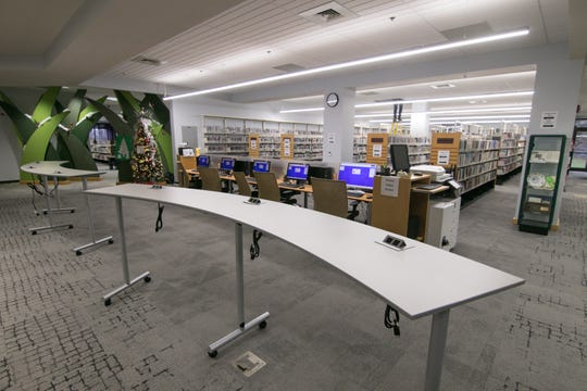 Movable standing-height laptop stations delineate space used for media and fiction in the Brighton District Library, shown Wednesday, Dec. 4, 2019.