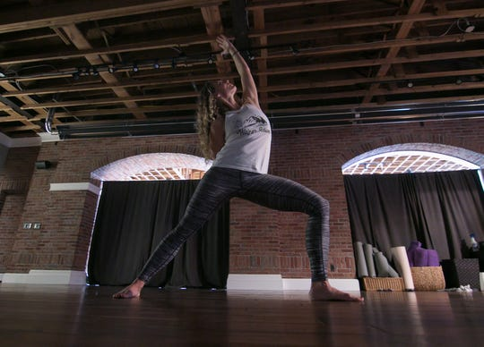 Tanya Pence, operating manager of the Brighton Yoga Center, takes a warrior pose in her new downtown Brighton studio space, shown Wednesday, Dec. 4, 2019.