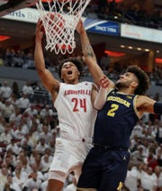 Louisville's Dwayne Sutton is fouled by Michigan's Isaiah Livers on his way to the basket on Dec. 3, 2019