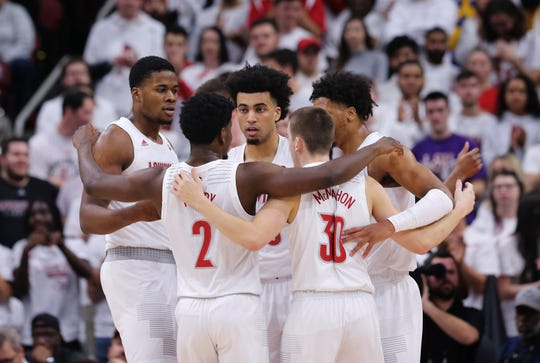 Louisville players huddled during a break in play against No. 4 Michigan in Louisville, Ky. on Dec. 3, 2019.