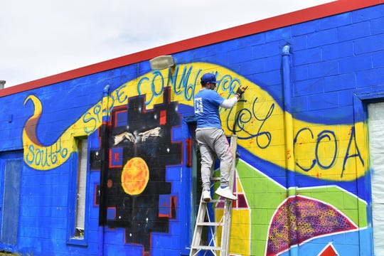 REALTOR® Frank Vicenté, busy working on a mural in Lansing